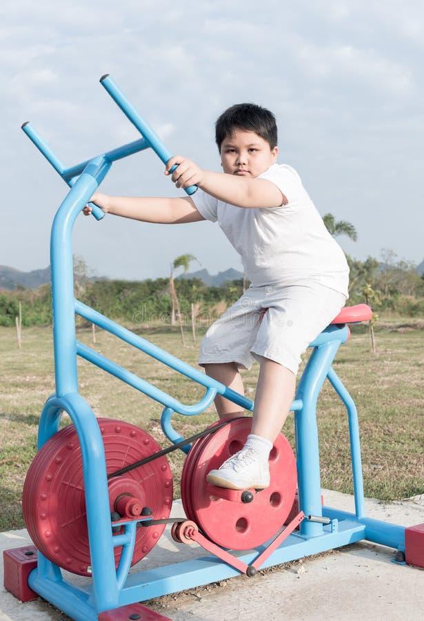 Ejercicio gordo obeso del muchacho en el parque de la salud pública imagen de archivo