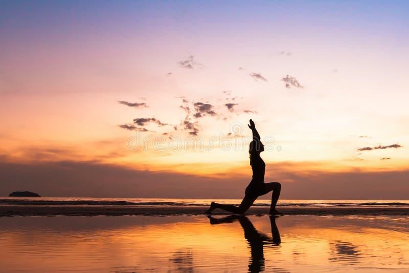 Ejercicio hermoso de la yoga en la playa en la puesta del sol imagenes de archivo
