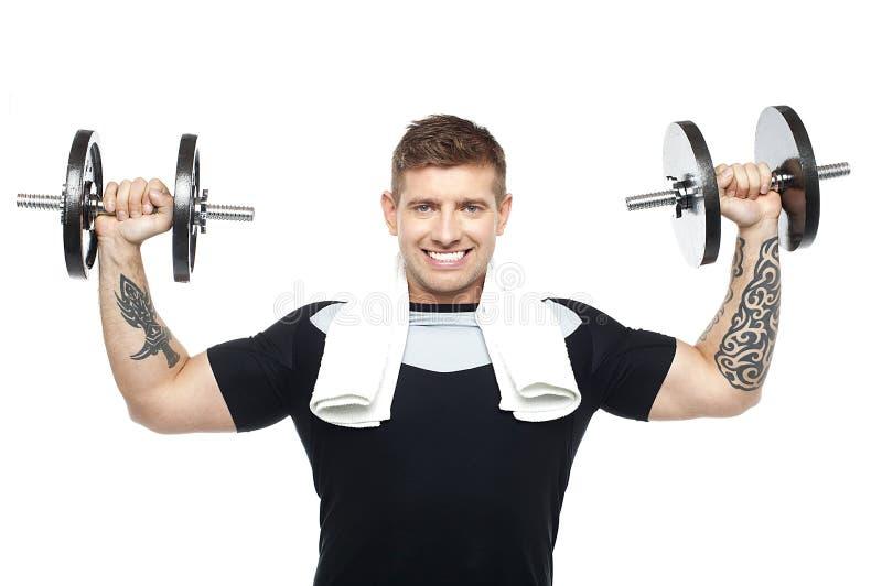 Ejercicio joven del bodybuilder, entonando su bíceps foto de archivo libre de regalías