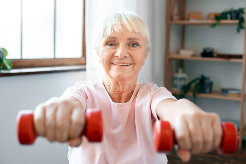 Ejercicio mayor de la mujer en casa que se sienta en bola del ejercicio con pesas de gimnasia en primer delantero imagenes de archivo