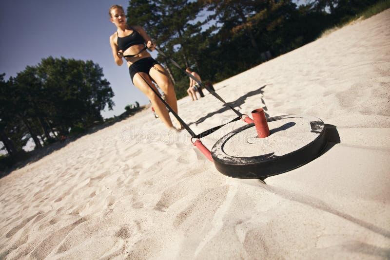 Ejercicio practicante del crossfit de la mujer en la playa imagen de archivo libre de regalías