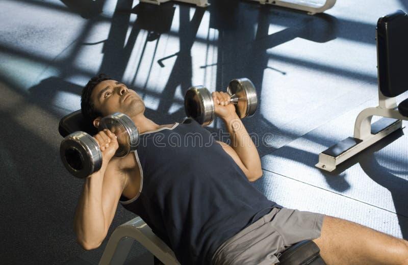 Ejercicio resuelto con pesas de gimnasia en club foto de archivo libre de regalías