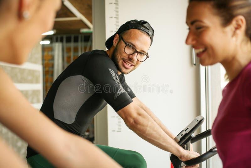 Ejercicio sonriente de dos personas jovenes en gimnasio fotografía de archivo libre de regalías