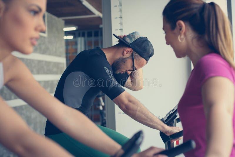 Ejercicio sonriente de dos personas jovenes en gimnasio fotos de archivo libres de regalías