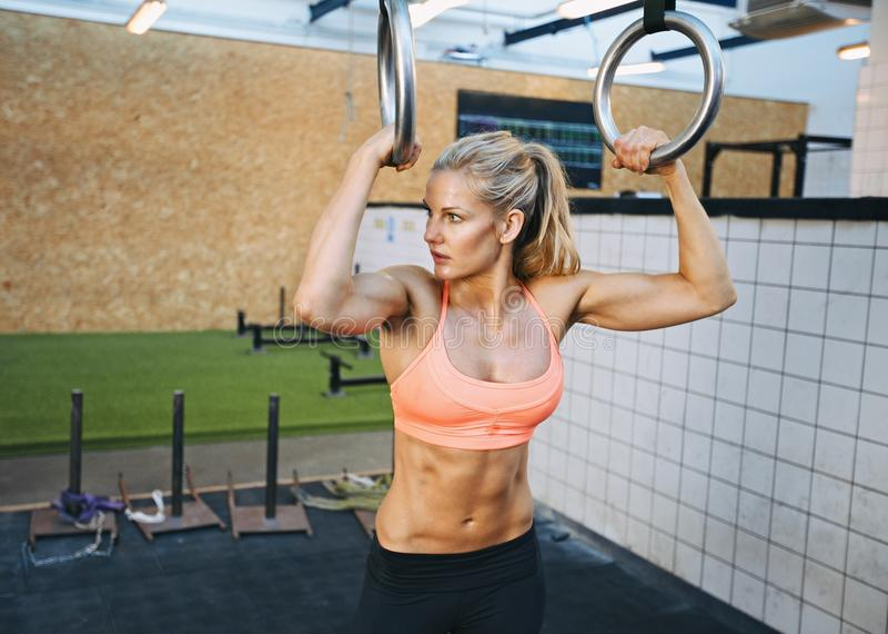 Ejercicios aptos de la mujer joven con los anillos del gimnasta imagen de archivo libre de regalías