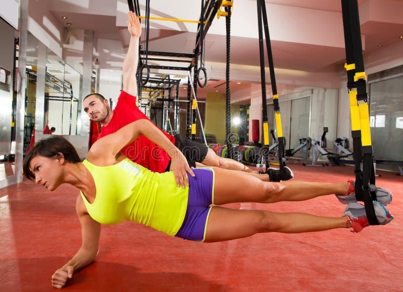 Ejercicios de formación de la aptitud TRX en la mujer y el hombre del gimnasio imagenes de archivo