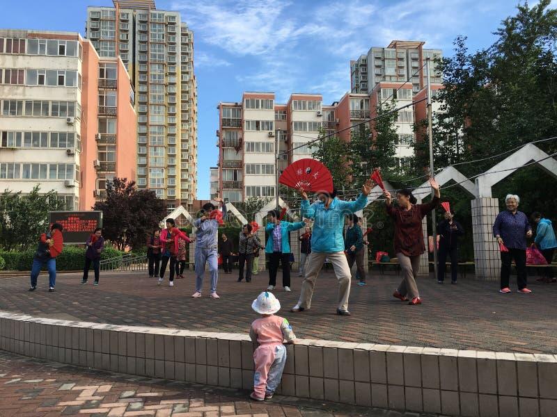 Ejercicios de la danza de Taiji de la mañana de la comunidad imagenes de archivo