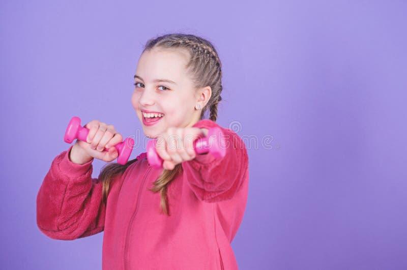 Ejercicios de la pesa de gimnasia del principiante Fondo violeta de la peque?a pesa de gimnasia del control del ni?o Deporte por  fotos de archivo