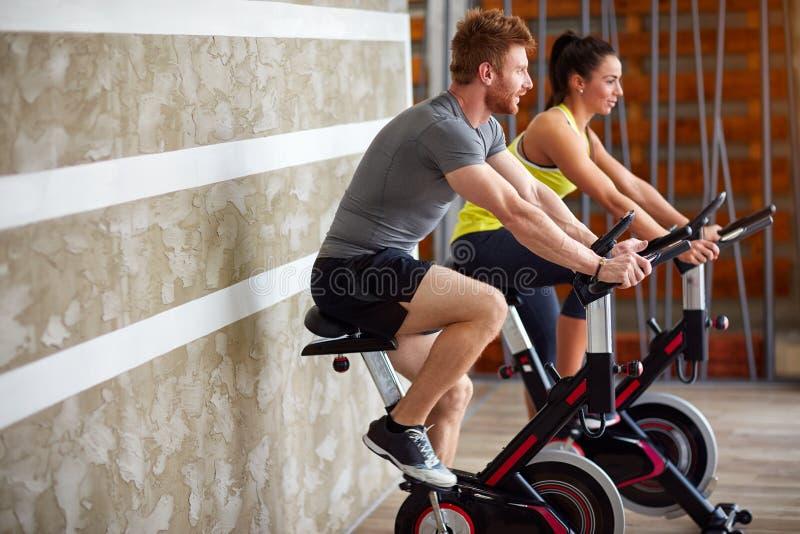 Ejercicios de los pares en la bici en gimnasio fotos de archivo libres de regalías