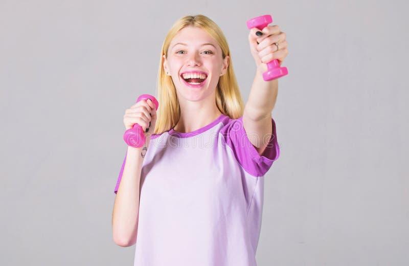 Ejercicios del b?ceps para la hembra Pesa de gimnasia del control de la muchacha Instructor de la aptitud Concepto sano de la for foto de archivo libre de regalías