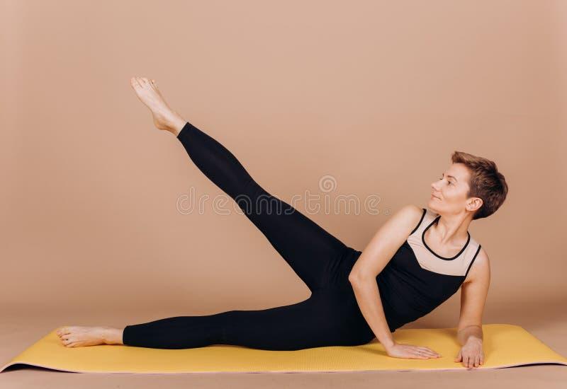 Ejercicios del carimat de los pilates de la yoga de la aptitud del deporte de la muchacha imagen de archivo libre de regalías