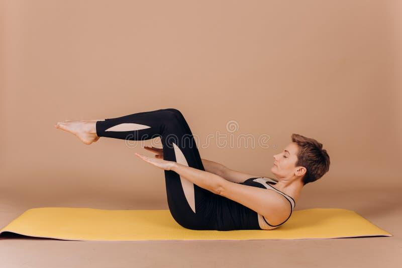 Ejercicios del carimat de los pilates de la yoga de la aptitud del deporte de la muchacha imagen de archivo
