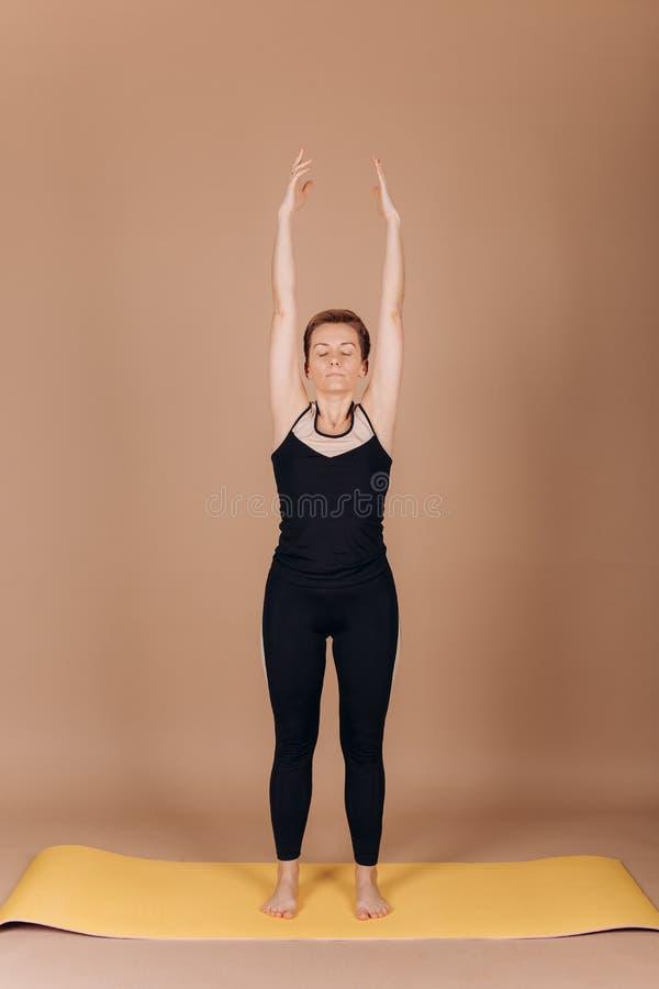 Ejercicios del carimat de los pilates de la yoga de la aptitud del deporte de la muchacha fotos de archivo