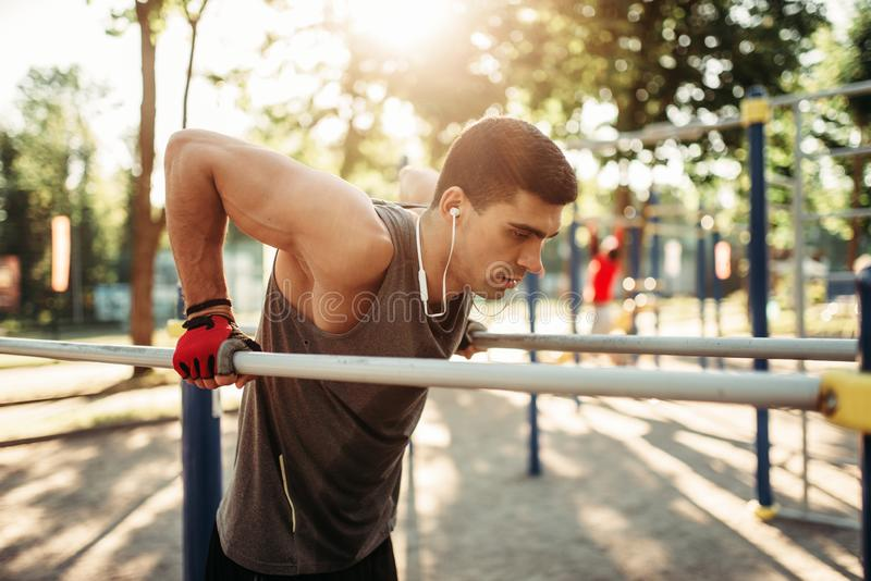 Ejercicios masculinos del atleta en las barrases paralelas al aire libre imagen de archivo