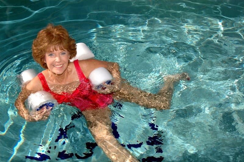 Ejercicios mayores de la piscina de la mujer