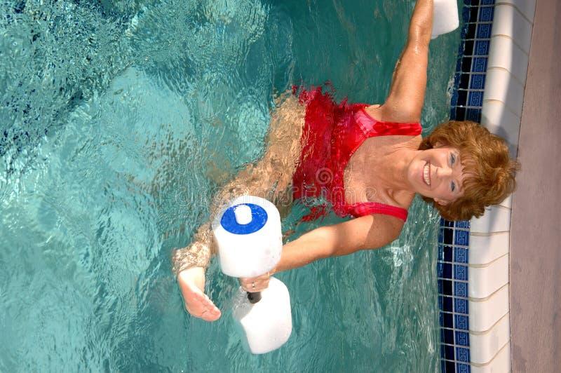 Ejercicios mayores de la piscina de la mujer foto de archivo