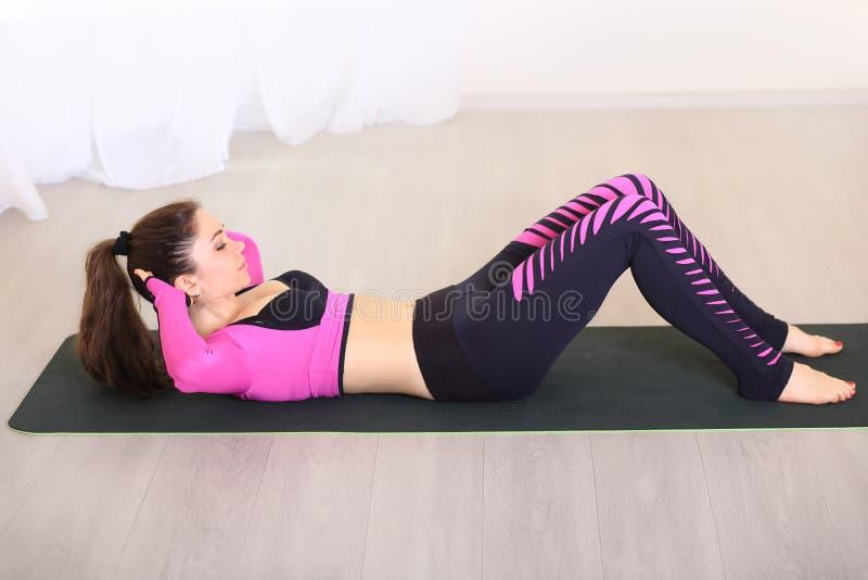 Ejercicios para los ABS la mujer joven entra para los deportes en el gimnasio fotos de archivo