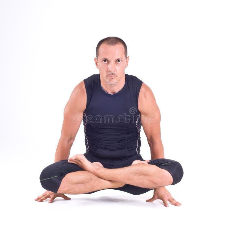 Ejercicios practicantes de la yoga:  Actitud de la escala - Tolasana foto de archivo
