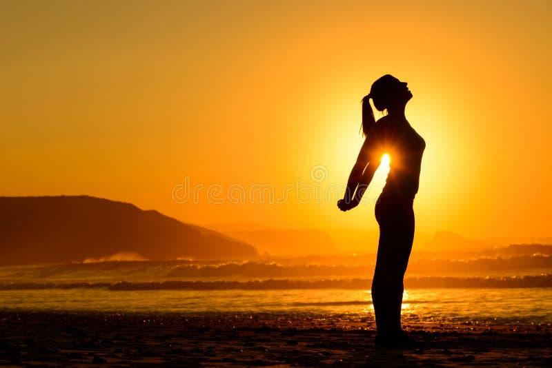 Ejercicios relajantes en la playa en la puesta del sol foto de archivo