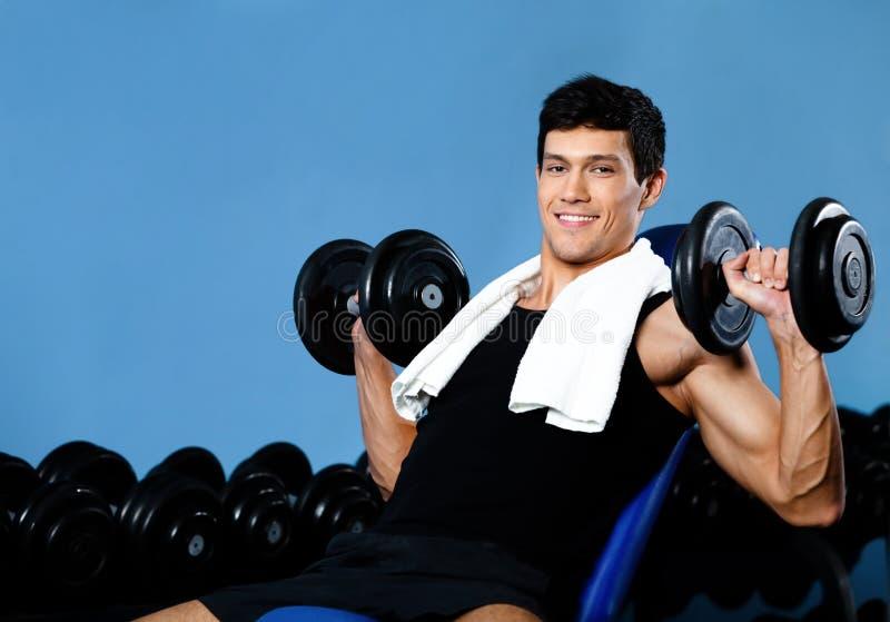 Ejercicios sonrientes del bodybuilder con los pesos fotos de archivo libres de regalías