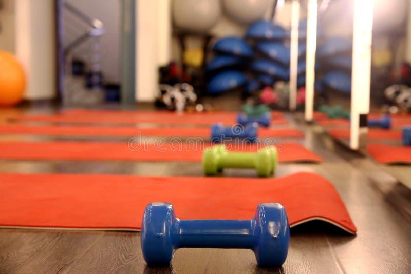 Ejercite la estera y las pesas de gimnasia en un gimnasio fotos de archivo libres de regalías