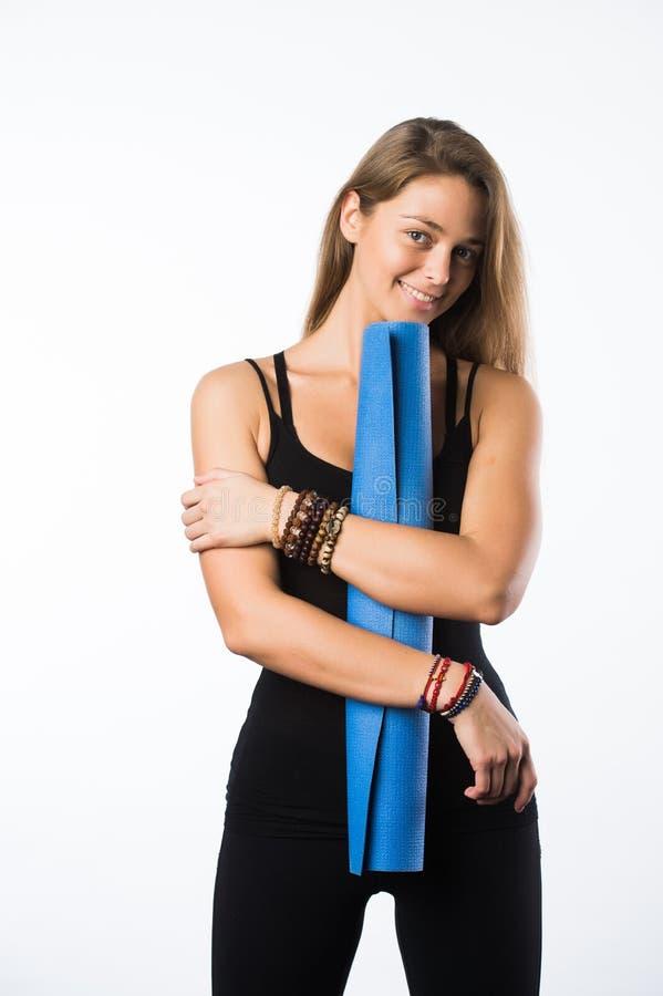 Ejercite a la mujer de la aptitud lista para la estera derecha de la yoga de la explotación agrícola del entrenamiento aislada en fotos de archivo