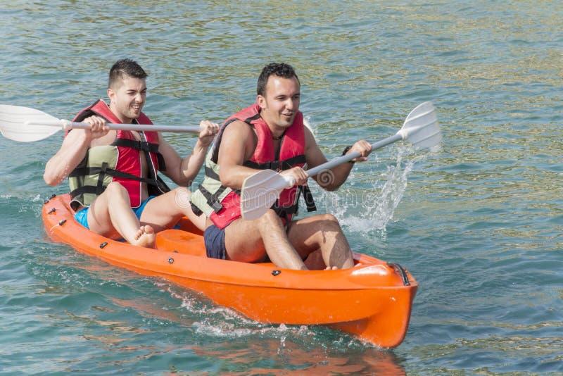 ejoying假期的两个年轻朋友,进来在有黄色独木舟的海 免版税图库摄影