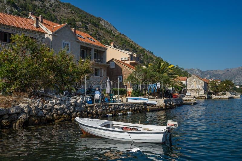 Eka som förtöjas på pir på sjösidan i den lilla Adriatiska havet staden Muo royaltyfria foton