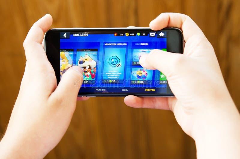 Ekaterimburgo, Rusia - 26 de julio de 2019: El muchacho juega las estrellas móviles libres de una reyerta del juego desarrolladas imagen de archivo