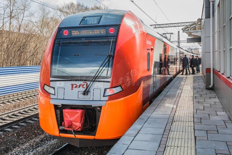 Ekaterimburgo, Sverdlovsk Rusia - 24 04 2019: El nuevo tren eléctrico rojo y anaranjado Lastochka ha llegado un nuevo ferrocarril fotos de archivo libres de regalías