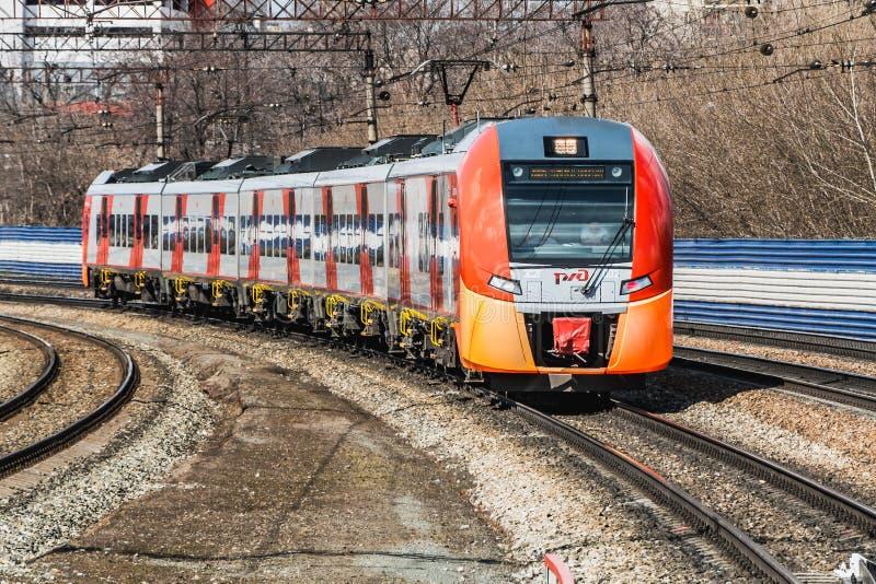 Ekaterimburgo, Sverdlovsk Rusia - 24 04 2019: El nuevo tren eléctrico rojo y anaranjado Lastochka llega un nuevo ferrocarril del fotos de archivo