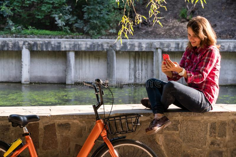 Ekologisk cykeltransport för ämne Den unga Caucasian kvinnan i skjortastudent sitter att vila i parkerar nära sjön för hyraapelsi royaltyfria bilder