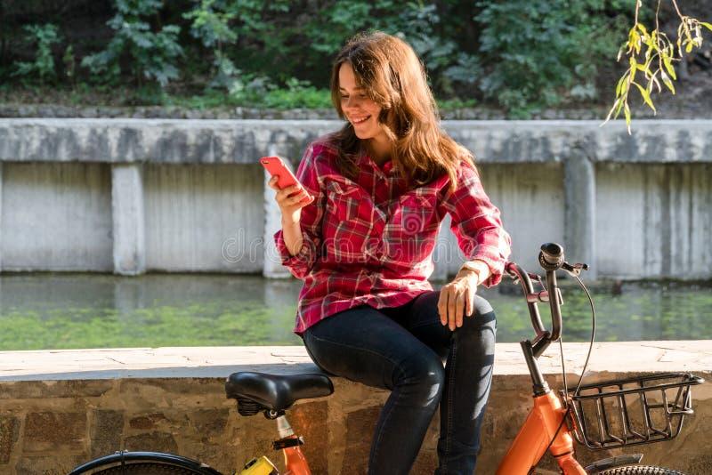 Ekologisk cykeltransport för ämne Den unga Caucasian kvinnan i skjortastudent sitter att vila i parkerar nära sjön för hyraapelsi royaltyfri foto