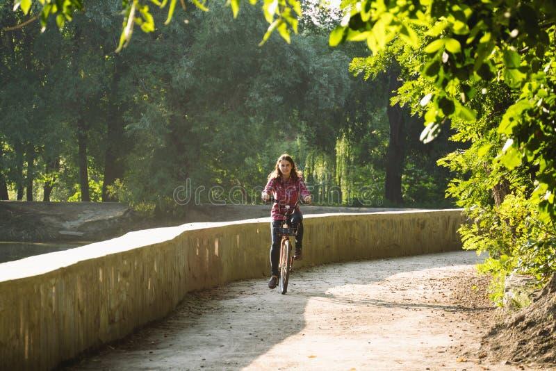 Ekologisk cykeltransport för ämne Den unga Caucasian kvinnan som rider på en grusväg i, parkerar nära en sjö som hyr ett orangefä royaltyfria foton