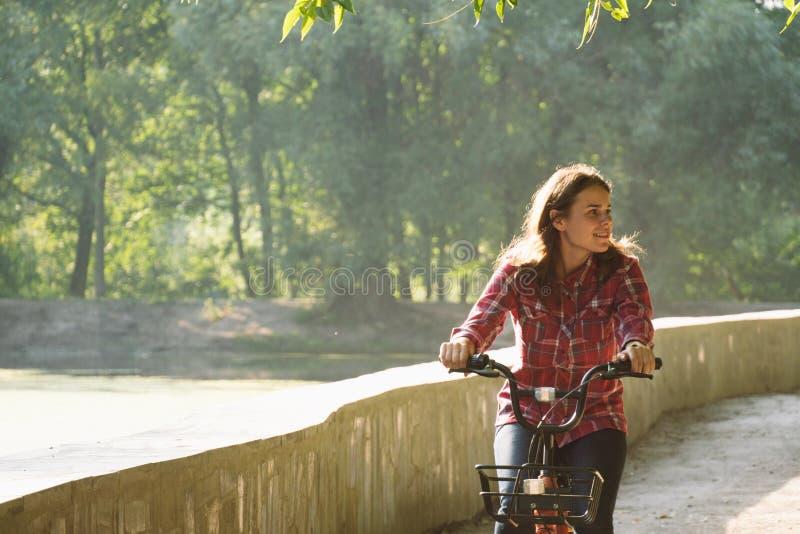 Ekologisk cykeltransport för ämne Den unga Caucasian kvinnan som rider på en grusväg i, parkerar nära en sjö som hyr ett orangefä arkivfoton