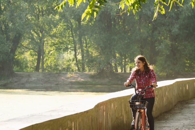 Ekologisk cykeltransport för ämne Den unga Caucasian kvinnan som rider på en grusväg i, parkerar nära en sjö som hyr ett orangefä arkivbild