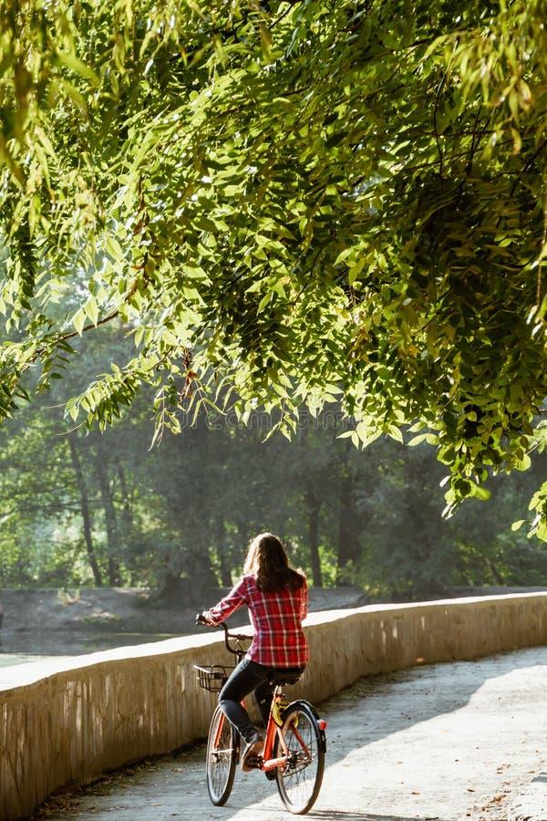 Ekologisk cykeltransport för ämne Den unga Caucasian kvinnan som rider på en grusväg i, parkerar nära en sjö som hyr ett orangefä arkivfoto