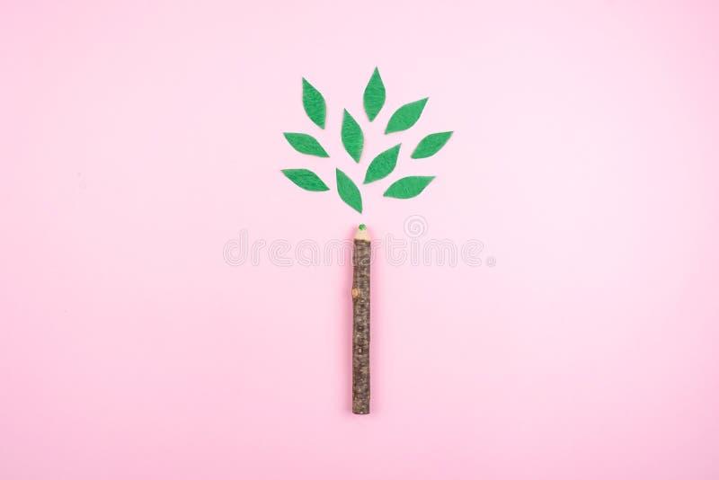 Ekologisk vänskapsmatch, hållbar miljö, Eco medvetet begrepp med pennan i form av en trädstam med gröna sidor på rosa färger royaltyfria foton