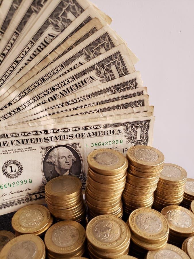 ekonomisk tillväxt och handeln, staplade mynt av tio mexikanska pesos och amerikanen en dollar räkningar arkivbild