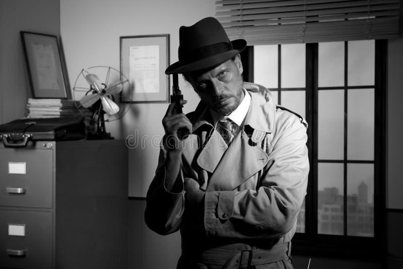 Ekranowy noir: detektyw trzyma pozować i kolt zdjęcia royalty free