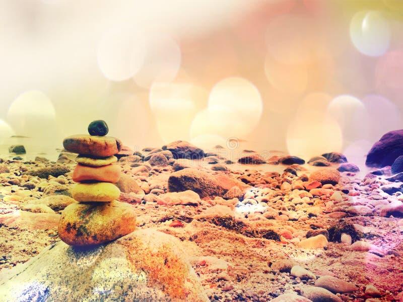 Ekranowy skutek Zrównoważony kamienny ostrosłup na dennym brzeg, fala w tle Kolorowi mieszkanie kamienie dla medytaci lying on th fotografia stock