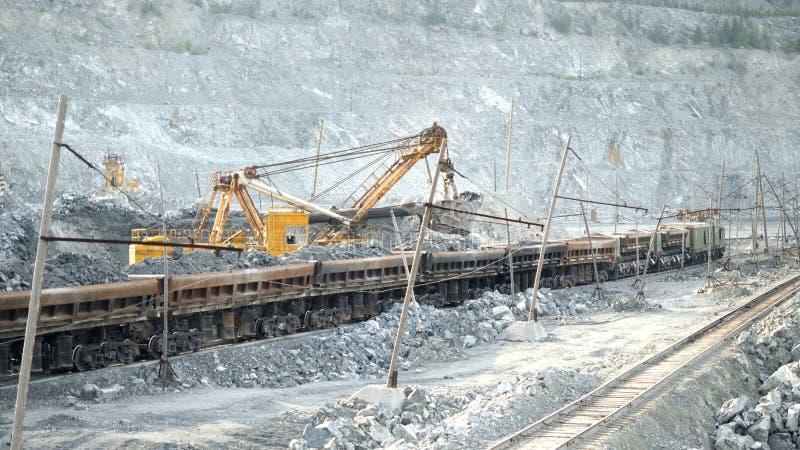Ekskawator i kolej z kruszec Ekskawator wypełnia z rudnymi sztachetowymi samochodami w tle otwarta jama Ciężki transport w kopaln zdjęcia stock