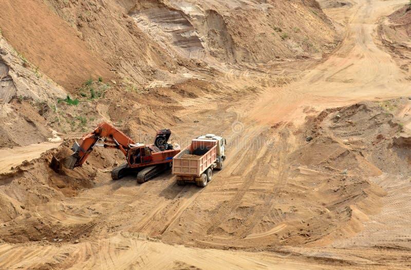 Ekskawator rozwija piasek na ładowaniu i odkrywkowym ciężka usyp ciężarówka ja obrazy royalty free