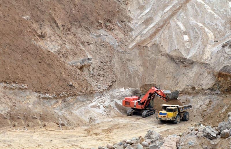 Ekskawator rozwija piasek na ładowaniu i odkrywkowym ciężka usyp ciężarówka ja obrazy stock