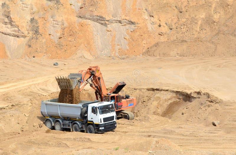 Ekskawator rozwija piasek na ładowaniu i odkrywkowym ciężka usyp ciężarówka ja fotografia royalty free
