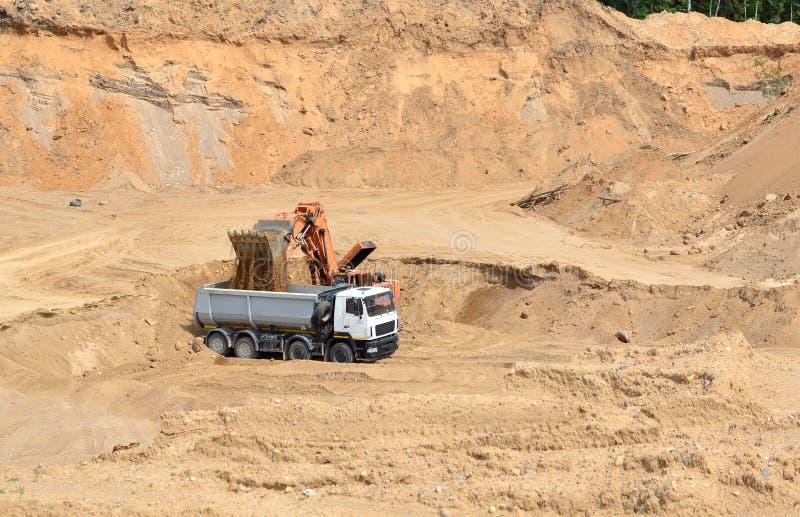 Ekskawator rozwija piasek na ładowaniu i odkrywkowym ciężka usyp ciężarówka ja zdjęcie stock