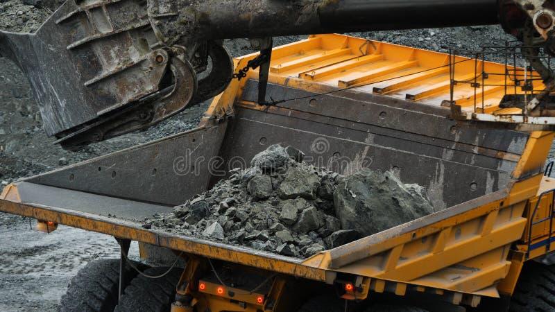 Ekskawator wypełnia usyp ciężarówkę Wiadro ekskawatoru zbliżenie ładuje kamienie w ciało usyp ciężarówka na kopalnictwie lub budo zdjęcia stock