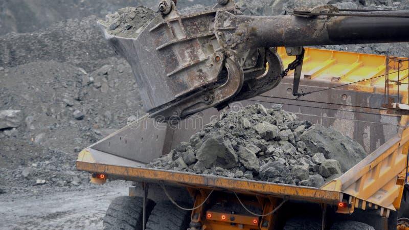 Ekskawator wypełnia usyp ciężarówkę Wiadro ekskawatoru zbliżenie ładuje kamienie w ciało usyp ciężarówka na kopalnictwie lub budo zdjęcie royalty free