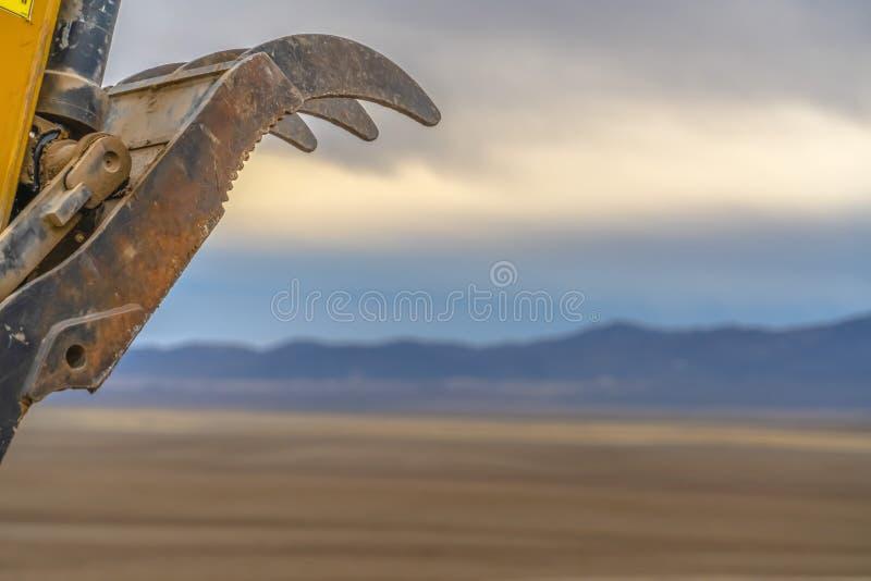Ekskawatoru wiadra zęby przeciw sylwetkowej góry i chmurnego nieba tłu obraz stock