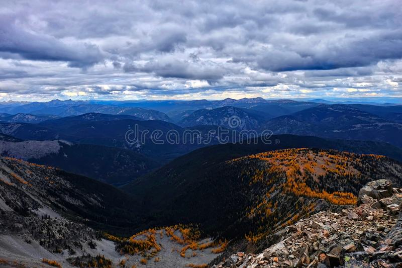 Ekspansywny krajobraz z halnymi graniami i żółtymi drzewami pod burzy niebem zdjęcia royalty free